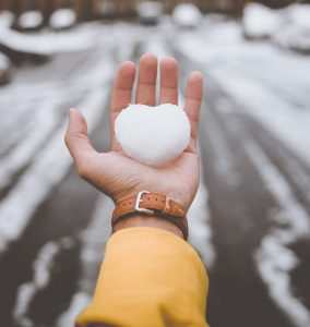 Hand holding a heart made from snow